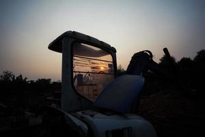 silueta de tractor y vehículo en el sitio de construcción foto