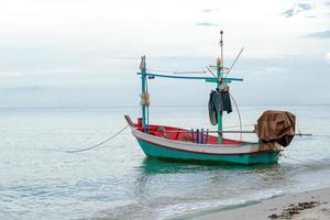 Pequeño barco de pesca tradicional flotando en el mar en la costa con superficie tranquila foto