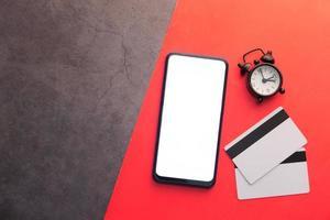 teléfono inteligente con pantalla en blanco sobre fondo rojo y negro foto
