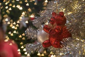 Abstract background of glittering bokeh lights with blurred ornament on the silver Christmas tree in foreground photo