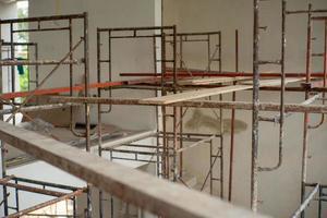 Placa de madera de enfoque selectivo en el andamio para trabajar a alto nivel en el sitio de construcción foto