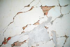 Abstract texture and background of broken plastered cement wall with red bricklayers inside