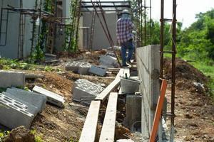 El enfoque selectivo de la pared de ladrillos de cemento y acero de refuerzo con trabajadores borrosa en segundo plano en el sitio de construcción foto
