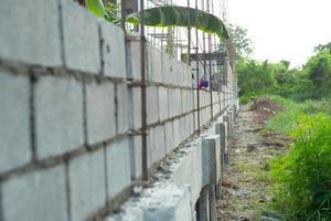 El paisaje del sitio de construcción con muro de albañil de hormigón y la mano del trabajador instalando los ladrillos en la pared en segundo plano. foto
