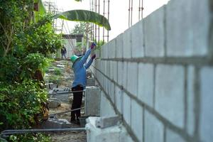 Perspective of concrete brick wall with worker installing the structure in background photo