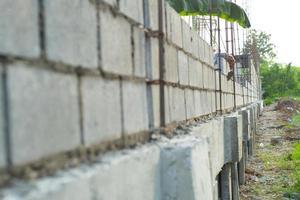 Paisaje del sitio de construcción con muro de albañil de hormigón y la mano del trabajador instalando los ladrillos en la pared foto