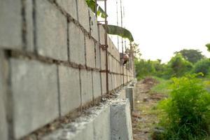 Paisaje del sitio de construcción con muro de albañil de hormigón y mano borrosa del trabajador instalando los ladrillos en la pared en segundo plano. foto