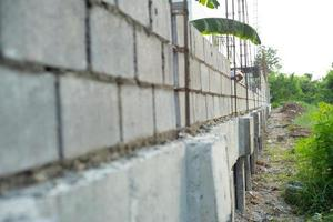 Landscape of construction site with concrete bricklayer wall and hand of worker installing the bricks on the wall in background.