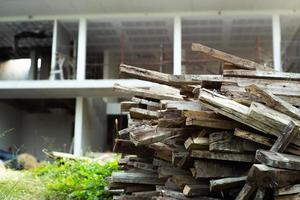 Closeup pile of wood with blurred house under construction in background photo