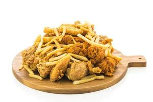 Papas fritas y pollo frito en placa de madera