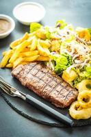 Filete de carne de ternera a la parrilla con patatas fritas aro de cebolla con salsa y verduras frescas