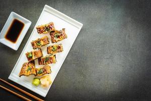 Rollo de maki de sushi de anguila a la parrilla o pescado unagi con salsa dulce