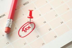 concepto de día de impuestos con círculo rojo en la fecha del calendario foto