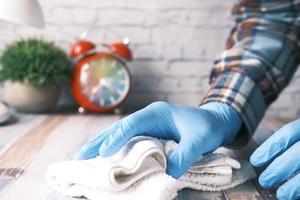 Mano de la persona en guantes desechables usando spray desinfectante para limpiar la superficie de la mesa foto