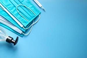Mascarillas quirúrgicas, termómetro y desinfectante de manos sobre fondo azul. foto
