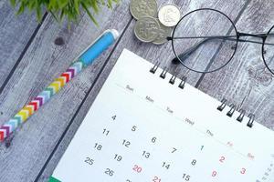 calendario y bolígrafo en el escritorio de madera foto