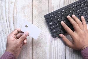Man using credit card to buy something online photo