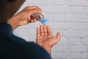 Mano usando gel desinfectante para prevenir virus. foto