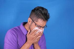 Hombre de camisa morada estornudando sobre fondo azul.