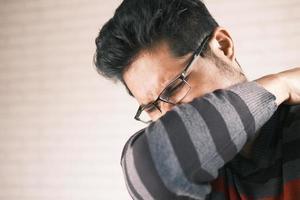 Man sneezing into elbow photo