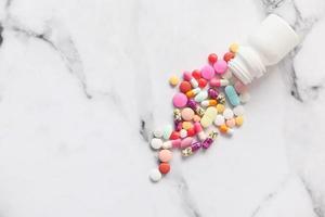 Pastillas de colores derramándose sobre fondo de mármol blanco foto