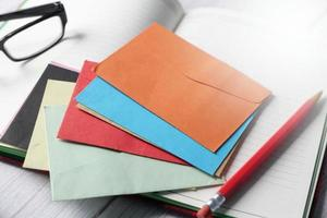 sobres de colores y bloc de notas en la mesa foto