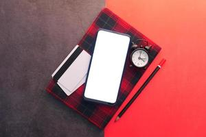 Smart phone, credit cards, and notebook on red and black background photo