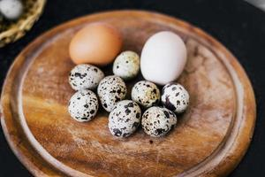 Quail and hen eggs on a wooden plate