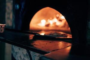 Pizza being placed in a pizza oven photo