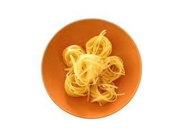 Pasta en un tazón de naranja aislado sobre un fondo blanco. foto