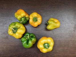 Yellow and green bell peppers on a wooden table background