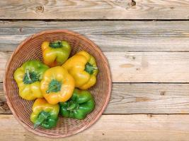 Yellow and green bell peppers in a wicker bowl on a wooden table background