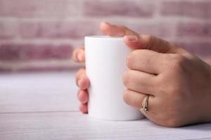 Close up of women's hand holding white color coffee cup photo