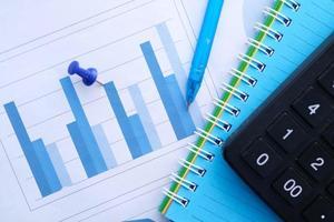 gráfico financiero, calculadora y bloc de notas en la mesa