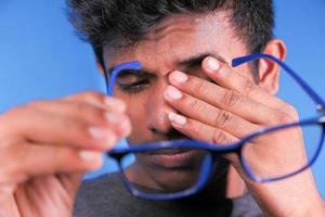 Cerca del hombre molesto que sufre de un fuerte dolor en los ojos foto