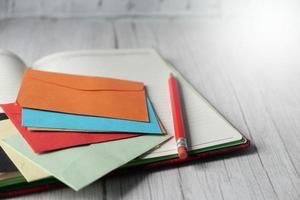 Sobre de colores y el bloc de notas en la mesa de madera foto