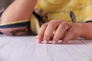 Close up of young woman's hands on table photo