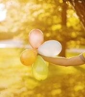Person holding balloons in sunlight