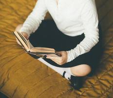 Mujer joven sentada en la cama mientras lee un libro foto