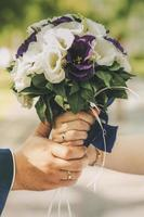 Couple holding a white and purple bouquet