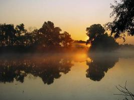 Fog and sunrise on the river photo