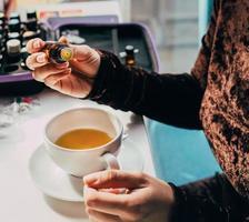 Adding oil to herbal tea photo