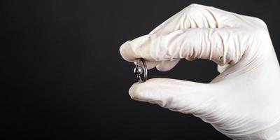 Piercing de plata anillo de joyería en la mano sobre fondo oscuro de cerca foto