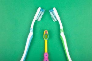 Set of toothbrushes for the whole family on green background photo