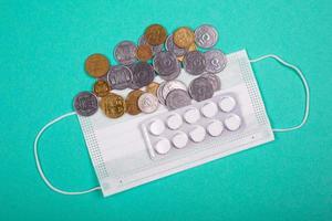 Aumento de los precios de las máscaras médicas, la máscara protectora y un puñado de monedas sobre un fondo azul. foto