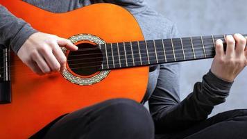 niña toca una guitarra acústica de color naranja sobre un fondo gris foto