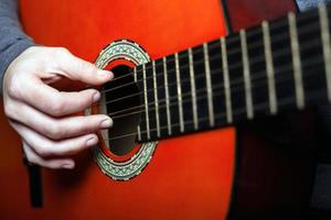 A woman learns to play a six-string classical acoustic guitar photo