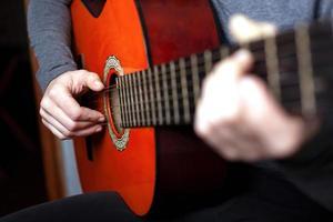 niña tocando una guitarra acústica foto