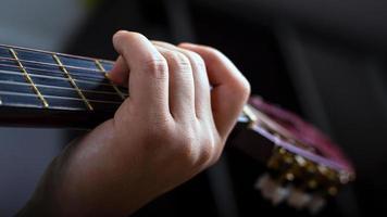 mano masculina sostiene un acorde en una guitarra acústica de seis cuerdas foto