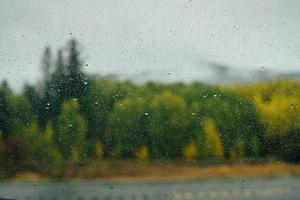 Raindrops on window with autumn background photo